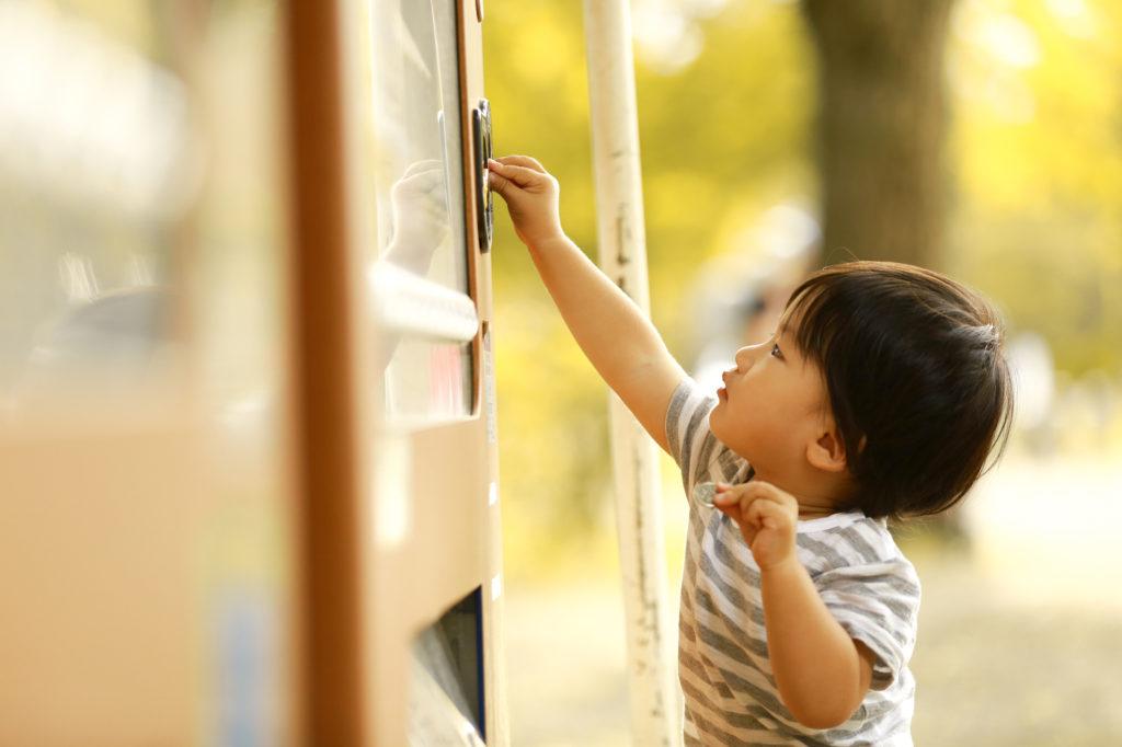 自動販売機でジュースを買う子どもの写真